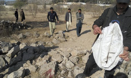 Pakistani security officials examine the site of the suicide bombing in Hangu. Photograph: Basit Shah/AFP/Getty Images