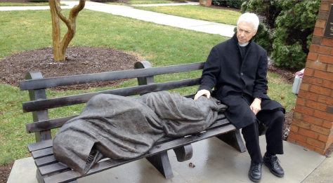 Rev. David Buck sits with the sculpture in front of his church (Photo: John Burnett/NPR)