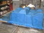 """Lay up fibreglass onto the mold to create the custom tub."""
